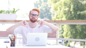 Pulgares abajo por el hombre que se sienta en la oficina al aire libre, pelos rojos Imagen de archivo libre de regalías