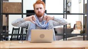 Pulgares abajo por el hombre que trabaja en el ordenador portátil Imagen de archivo libre de regalías