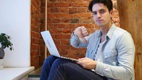 Pulgares abajo por el hombre que trabaja en el ordenador portátil, oficina del desván Foto de archivo libre de regalías