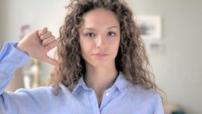 Pulgares abajo por la mujer del pelo rizado en el trabajo, mirando la cámara almacen de video