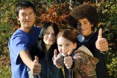 Pulgares adolescentes étnicos para arriba Imagenes de archivo