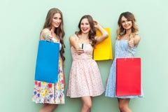 Pulgares adultos jovenes de las muchachas para arriba, shooing la tarjeta de crédito, sosteniendo los paquetes y esperando vierne Imagen de archivo