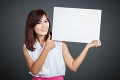 Pulgares asiáticos de la muchacha para arriba para la muestra en blanco Foto de archivo