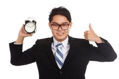 Pulgares asiáticos del hombre de negocios para arriba con el despertador Imagen de archivo libre de regalías