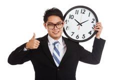 Pulgares asiáticos del hombre de negocios para arriba con un reloj Fotos de archivo