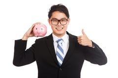 Pulgares asiáticos del hombre de negocios para arriba con una hucha rosada Foto de archivo libre de regalías