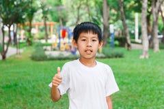 Pulgares asiáticos del muchacho para arriba Fotografía de archivo