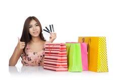 Pulgares asiáticos felices de la mujer para arriba con las tarjetas y los panieres de crédito fotografía de archivo libre de regalías