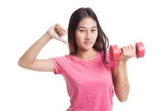 Pulgares asiáticos infelices de la mujer abajo con pesas de gimnasia Imagenes de archivo