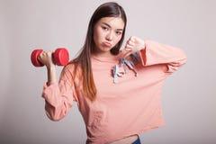 Pulgares asiáticos infelices de la mujer abajo con pesas de gimnasia Imagen de archivo libre de regalías