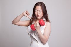 Pulgares asiáticos infelices de la mujer abajo con pesas de gimnasia Fotos de archivo