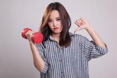 Pulgares asiáticos infelices de la mujer abajo con pesas de gimnasia Foto de archivo libre de regalías