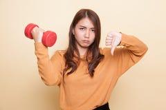 Pulgares asiáticos infelices de la mujer abajo con pesas de gimnasia Foto de archivo