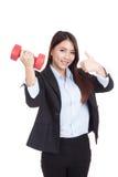 Pulgares asiáticos jovenes de la empresaria para arriba con pesa de gimnasia roja Imagenes de archivo