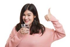 Pulgares asiáticos jovenes de la mujer para arriba con un vidrio de agua potable Imagenes de archivo