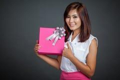Pulgares asiáticos hermosos de la muchacha para arriba con una caja de regalo Fotografía de archivo