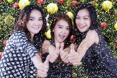 Pulgares de la demostración de las muchachas para arriba con la decoración de la Navidad Imagenes de archivo