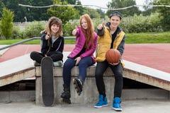 Pulgares de los adolescentes para arriba en el skatepark Imagenes de archivo