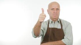 Pulgares del delantal de la cocina del hombre que llevan encima del buen trabajo imagen de archivo