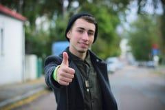 Pulgares del hombre joven para arriba en la calle Imagen de archivo