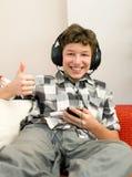 Pulgares del muchacho hasta buena música Fotografía de archivo libre de regalías
