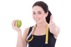 Pulgares deportivos atractivos jovenes de la mujer para arriba con la manzana y la medición Fotos de archivo