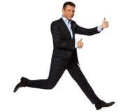 Pulgares dobles de salto de funcionamiento de un hombre de negocios para arriba Imágenes de archivo libres de regalías