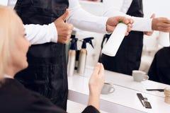 Pulgares femeninos de la demostración del estilista hasta mujer madura El peluquero recomienda el champú del pelo para la mujer Foto de archivo