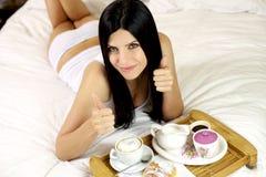 Pulgares hermosos de la muchacha para arriba durante el desayuno en cama Fotos de archivo libres de regalías