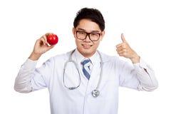 Pulgares masculinos asiáticos del doctor para arriba con la manzana Imágenes de archivo libres de regalías