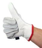 Pulgares para arriba con los guantes de un trabajo en la mano Foto de archivo libre de regalías
