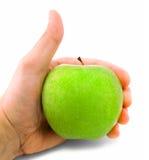 Pulgares para arriba con una manzana. Fotos de archivo