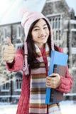 Pulgares-para arriba del suéter y de la demostración del estudiante universitario que llevan Imagen de archivo