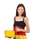 Pulgares para arriba. Estudiante hermoso con la blusa de la bandera de Alemania que sostiene los libros. Imagen de archivo