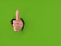 Pulgares para arriba que perforan a través del Libro Verde Fotos de archivo libres de regalías