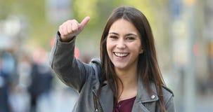 Pulgares que gesticulan adolescentes felices para arriba en la calle