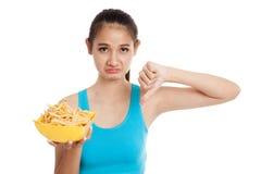 Pulgares sanos asiáticos de la muchacha abajo con las patatas fritas Fotos de archivo