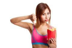 Pulgares sanos asiáticos de la muchacha abajo con las patatas fritas Foto de archivo