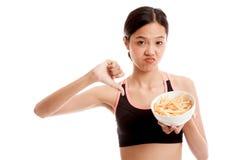 Pulgares sanos asiáticos de la muchacha abajo con las patatas fritas Fotos de archivo libres de regalías