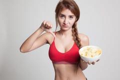 Pulgares sanos asiáticos de la muchacha abajo con las patatas fritas Fotografía de archivo