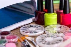 Pulimento, esmalte de uñas y accesorios de la lámpara Fotografía de archivo