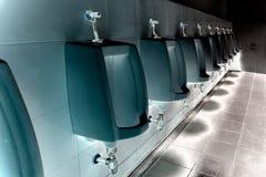 Pulisca gli uomini degli orinali nella toilette della stazione di servizio fotografia stock
