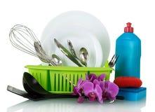 Pulisca i piatti e la coltelleria sullo stendipanni, vicino al detersivo per i piatti e la spugna, isolato su bianco Fotografia Stock