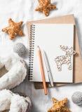 Pulisca il blocco note in bianco, gli ornamenti di natale, la renna di legno, i giocattoli, stivali domestici del ugg su un fondo Immagini Stock Libere da Diritti