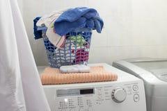 Pulisca il canestro di lavanderia sopra la lavatrice immagine stock