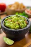 Pulisca il colpo verticale di una ciotola fresca di chip di tortiglia di stile del ristorante e del guacamole Immagine Stock Libera da Diritti