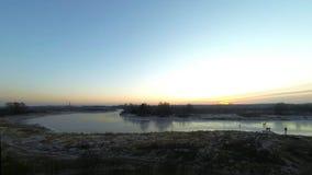 Pulisca il ghiaccio sul fiume Giro della gente sui pattini Timelapse Tramonto stock footage