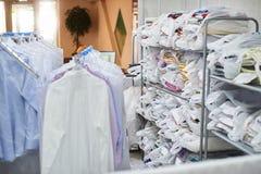 Pulisca l'abbigliamento imballato nei sacchetti di plastica sugli scaffali e pesa sui ganci Fotografia Stock Libera da Diritti