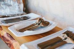 Pulisca la coltelleria: i cucchiai, le forchette, i coltelli nei supporti bianchi ed il vassoio confuso con i vetri stanno sullo  Fotografie Stock