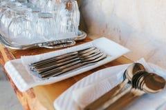 Pulisca la coltelleria: i cucchiai, le forchette, i coltelli nei supporti bianchi ed il vassoio confuso con i vetri stanno sullo  Fotografia Stock Libera da Diritti
